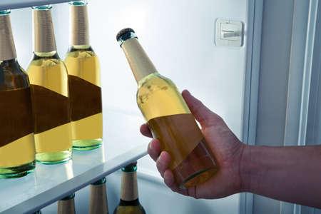 tomando refresco: Hombre que elige la botella de cerveza de una nevera Foto de archivo
