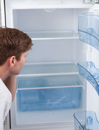 major depression: Portrait of a hungry man looking for food in refrigerator