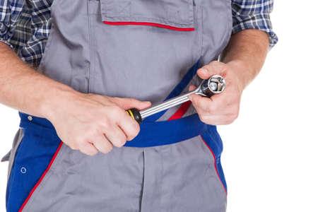 jumpsuit: Male mechanic holding ratchet isolated on white background
