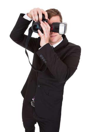 capturing: Portrait of paparazzi capturing photograph on white background