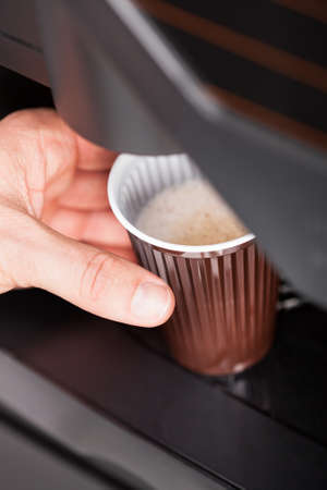 Coffee maker pouring hot espresso coffee in a glass photo