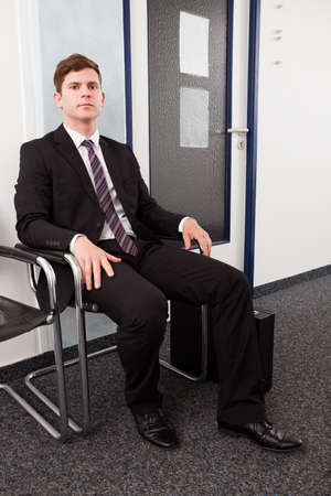 Anxious man waiting for job interview sitting on chair photo