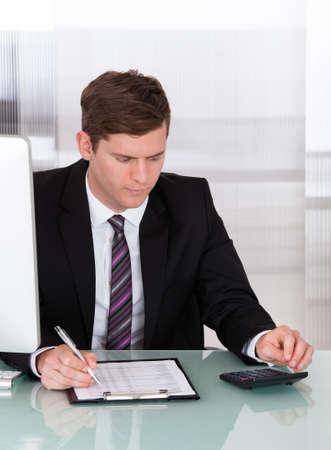 Portrait of businessman calculating finances in office photo