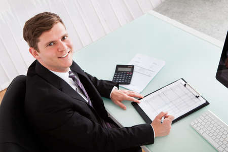 Portrait of happy businessman calculating finances in office photo