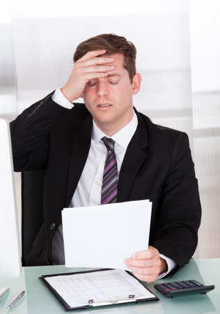 Portrait of Anxiety businessman sitting in office holding paper photo