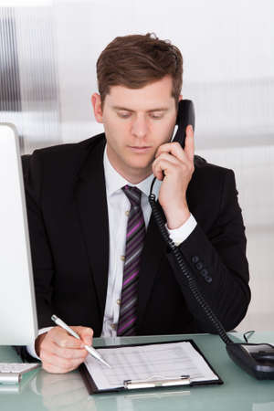 Portrait of businessman talking on telephone in office Stock Photo - 21477587