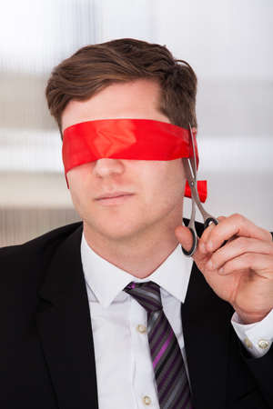Businessman cutting his blindfold with scissor in office photo