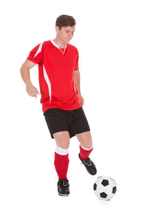 soccer boots: Portrait Of Young Soccer Player Kicking Ball Over White Background