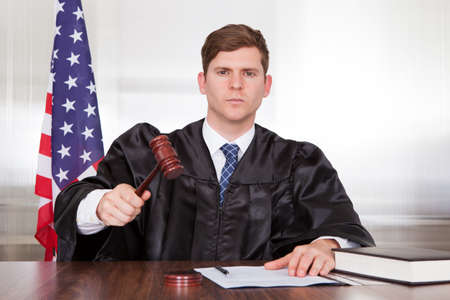 Male Judge With The Gavel And Book In Courtroom