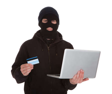 Burglar Wearing Mask Holding Credit Card And Laptop Over White Background photo