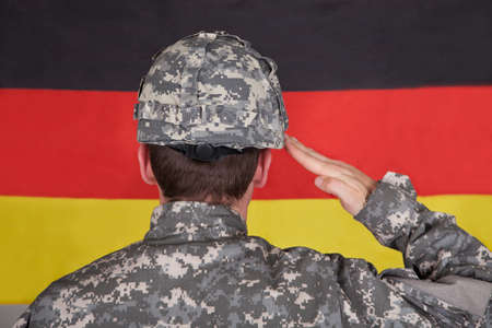 german soldier: Portrait Of Serious Solider Standing In Front Of German Flag