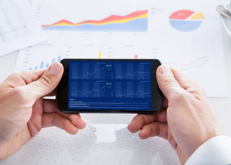 Businessman Analyzing Graph On Cell Phone In Office Stock Photo - 21477787