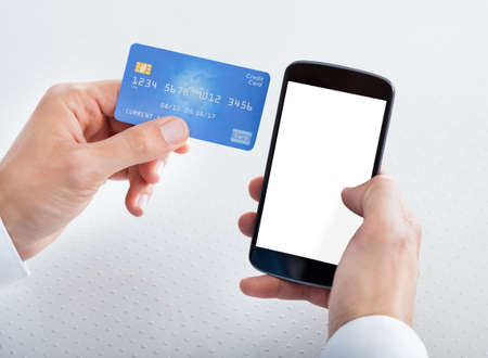 service card: Man Holding Credit Card And Cell Phone Checking Account Balance