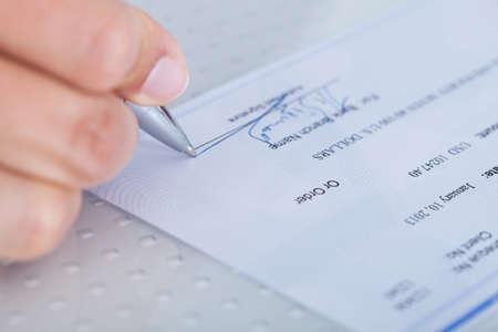 dinero falso: Una mano masculina rellenar el importe en un cheque
