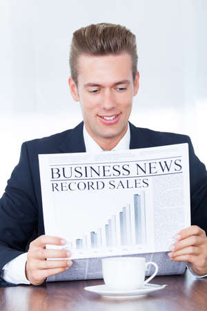 Happy Young Businessman Reading News On Newspaper photo