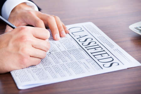 classifieds: Close-up Of Young Businessman Reading Classifieds On Newspaper Stock Photo