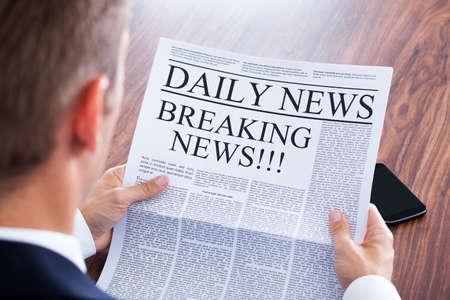 Jeune homme d'affaires lecture Nouvelles de dernière heure sur le journal Banque d'images