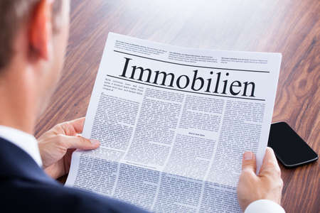 reading newspaper: Businessman Reading Newspaper With The Headline Real Estate Stock Photo