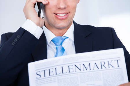 Businessman Reading Newspaper With The Headline Job Market Stock Photo - 21477836