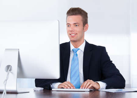 Portrait Of Happy Young Businessman Using Computer In Office Stock Photo - 21477845