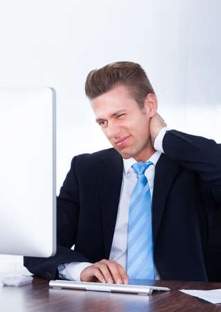 working stiff: Businessman Using Computer Suffering From Neck Ache Stock Photo