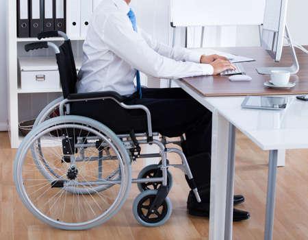 discapacidad: Empresario discapacitados Sentado en silla de ruedas y usa el ordenador en la oficina Foto de archivo