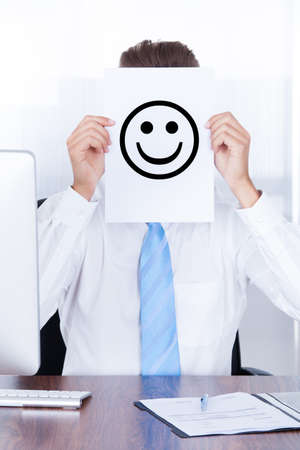 Close-up Businessman Holding Smiley Emoticon On Paper Over Face photo