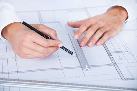 construction draftsman: Close-up Of Male Architect Working On Blueprint At Desk