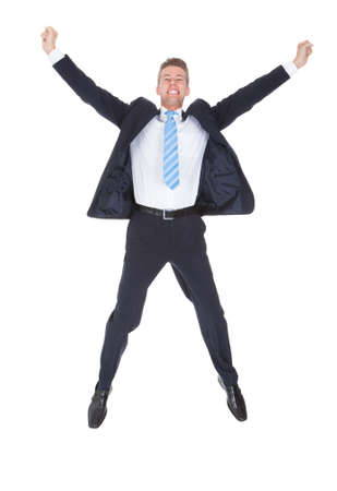 jump suit: Portrait Of Happy Young Excited Businessman Over White Background Stock Photo