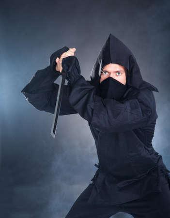 ninja weapons: Portrait Of Male Ninja In Black Costume Holding Sword Stock Photo