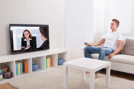 flatscreen: Young Man Sitting On Couch And Watching Movie At Home Stock Photo