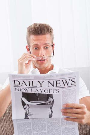 layoffs: Man Reading Newspaper With The Headline New Layoffs