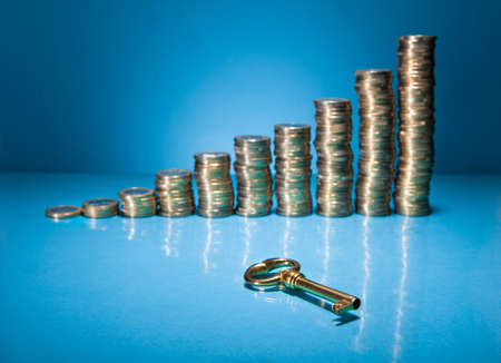 Stack Of Golden Coin And Key Over Blue Background photo