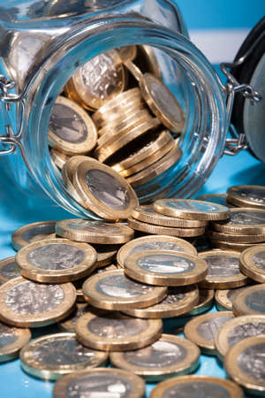 money jar: Euro Coins Spilling From A Money Jar Stock Photo