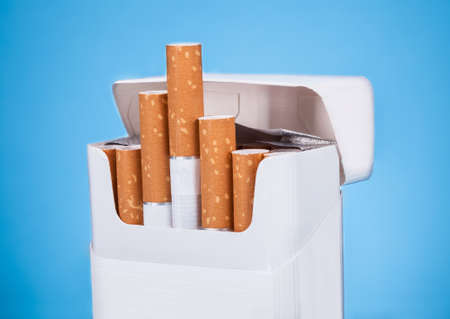 Photo Of Cigarettes In Pack Over Blue Background photo