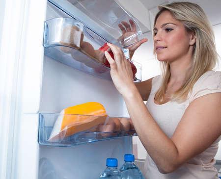mujer gorda: Joven buscando algo en frigorífico