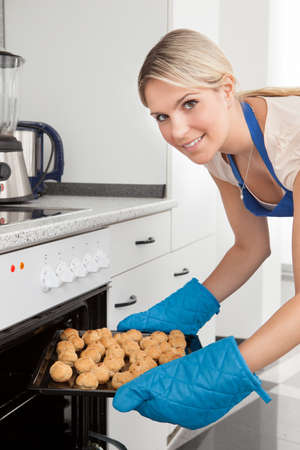 Young Woman Placing Tray Full Of Cookies In Oven photo