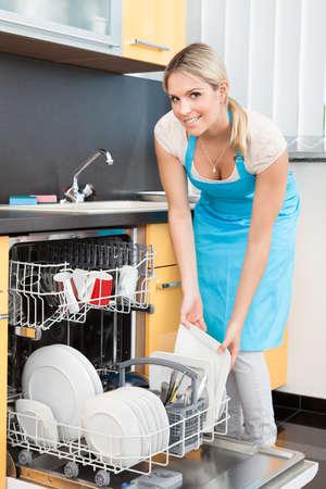 mandil: Mujer feliz que pone Utensilios Lavaplatos para la limpieza