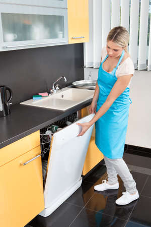 household tasks: Woman Closing Dishwashers Door In The Kitchen