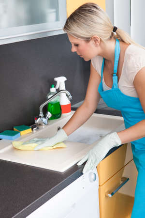 cleaning services: Portrait Of Happy Woman Cleaning Kitchen Worktop