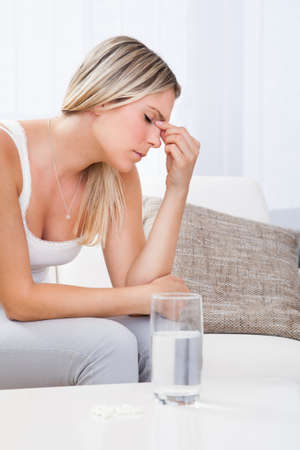 throbbing: Woman with a migraine sitting holding her throbbing head