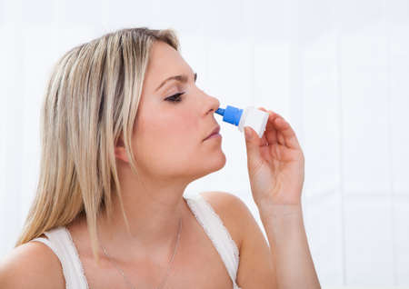 rheum: Close up of a Woman using nasal spray isolated on white background