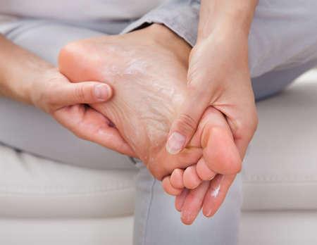 foot cream: Closeup of womans hand applying cream on feet Stock Photo