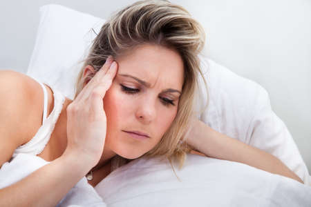 Portrait of woman with headache lying on bed photo