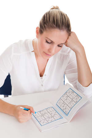 contemplated: Young Woman On White Background Solving Sudoku Stock Photo