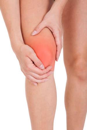 osteoarthritis: Cerca de la lesi�n en la pierna mujer aislada en el fondo blanco