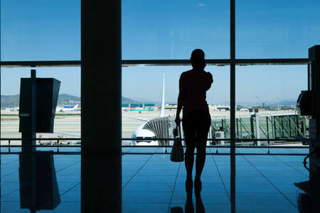 travellers: Silhouette of women talking on cell phone in airport terminal