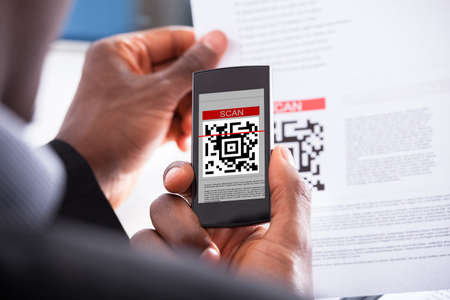 american media: Close-up Photo Of Businessman Hand Scanning Code Stock Photo