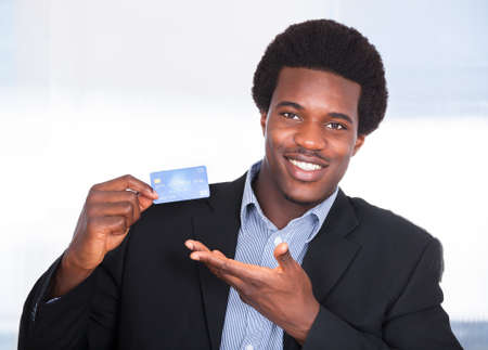 debts: Portrait Of Young Happy Businessman Holding Credit Card