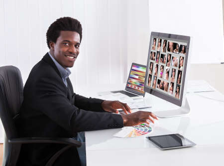 Portrait Of Happy Professional Businessman Editing Images In Office Stock Photo - 21478542